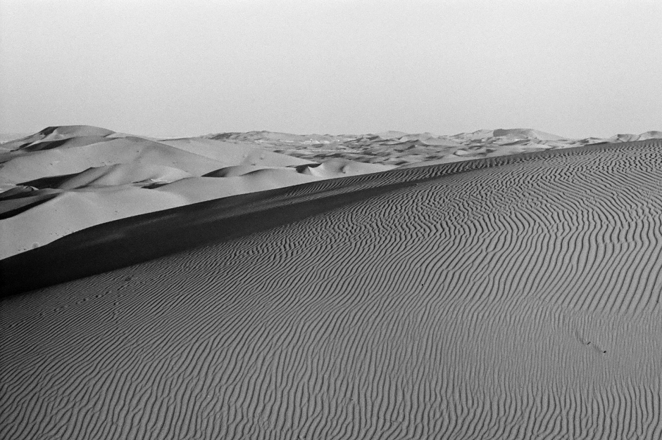 Broad expanse of sand with dunes to the horizon.
